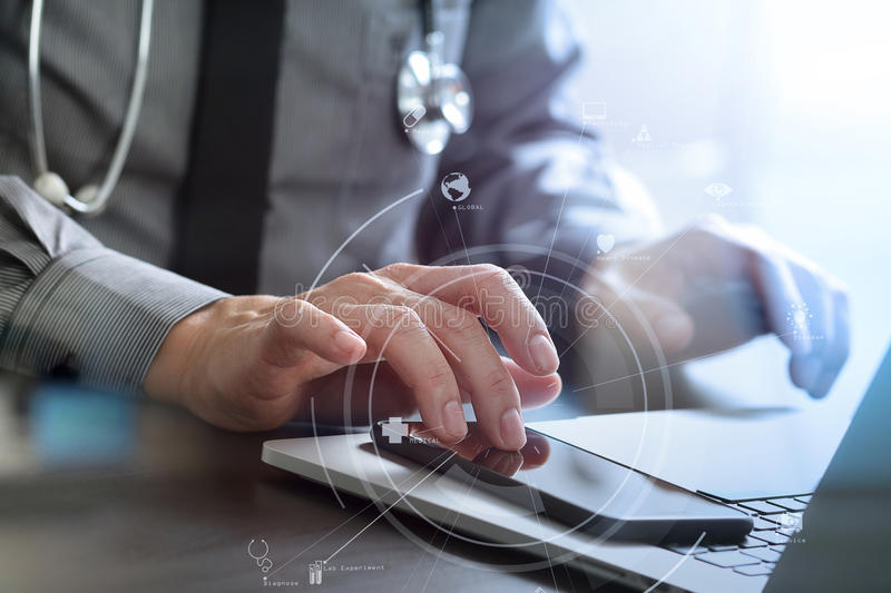 Close up of smart medical doctor working with mobile phone and l. Aptop computer and stethoscope on dark wooden desk with virtual reality icon diagram royalty free stock image