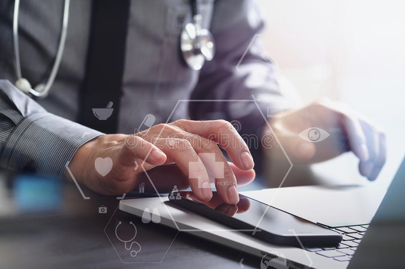 Close up of smart medical doctor working with mobile phone and l. Aptop computer and stethoscope on dark wooden desk with virtual reality icon diagram stock image