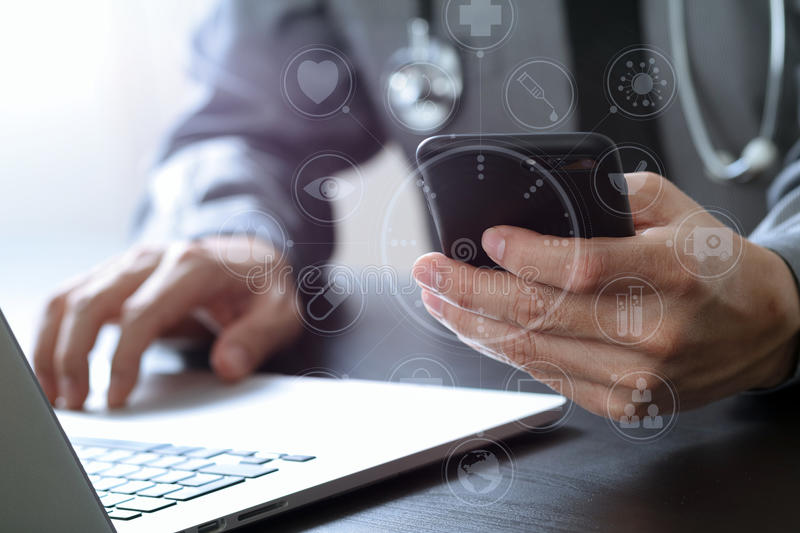 Close up of smart medical doctor working with mobile phone and l. Aptop computer and stethoscope on dark wooden desk with virtual reality icon diagram royalty free stock images