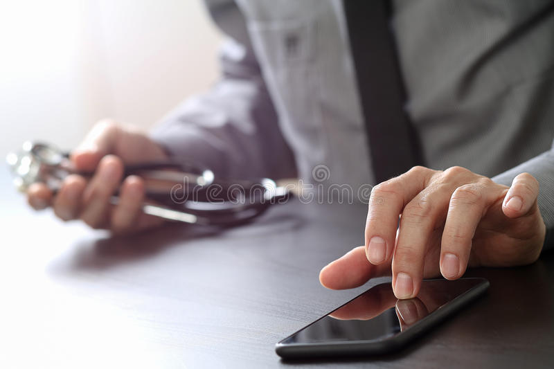 Close up of smart medical doctor working with mobile phone and s. Tethoscope on dark wooden desk stock photo