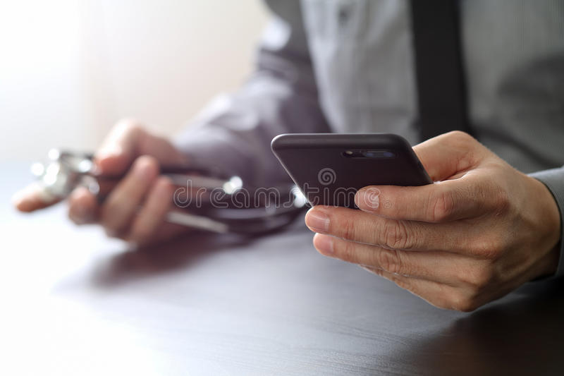 Close up of smart medical doctor working with mobile phone and s. Tethoscope on dark wooden desk stock images
