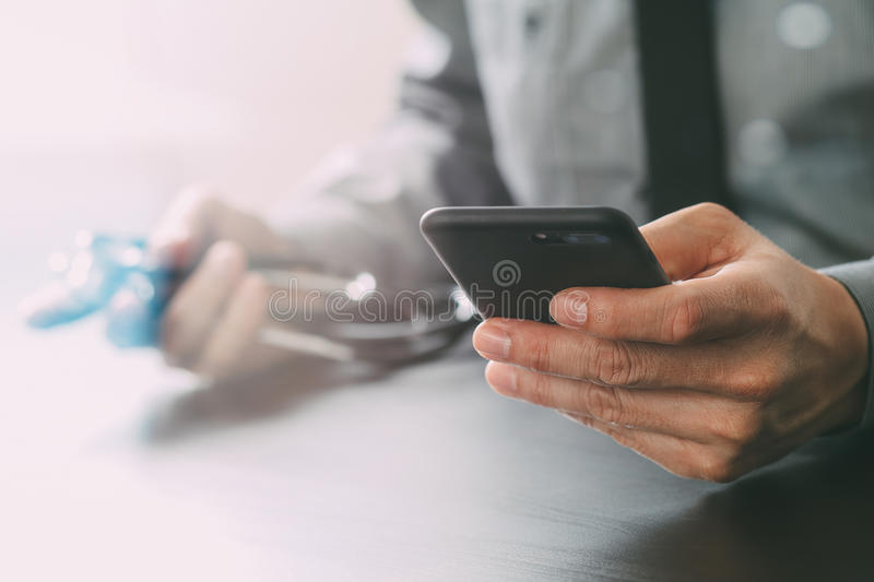 Close up of smart medical doctor working with mobile phone and s. Tethoscope on dark wooden desk stock image