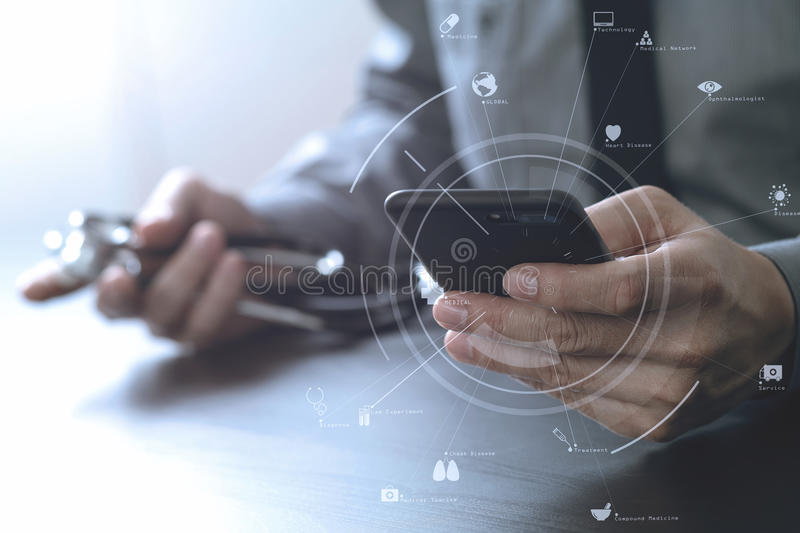 Close up of smart medical doctor working with mobile phone and s. Tethoscope on dark wooden desk with virtual reality icon diagram royalty free stock photo