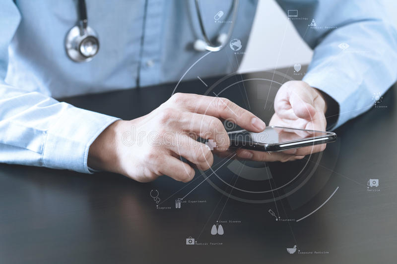 Close up of smart medical doctor working with smart phone and st. Ethoscope on dark wooden desk with virtual icon diagram royalty free stock image
