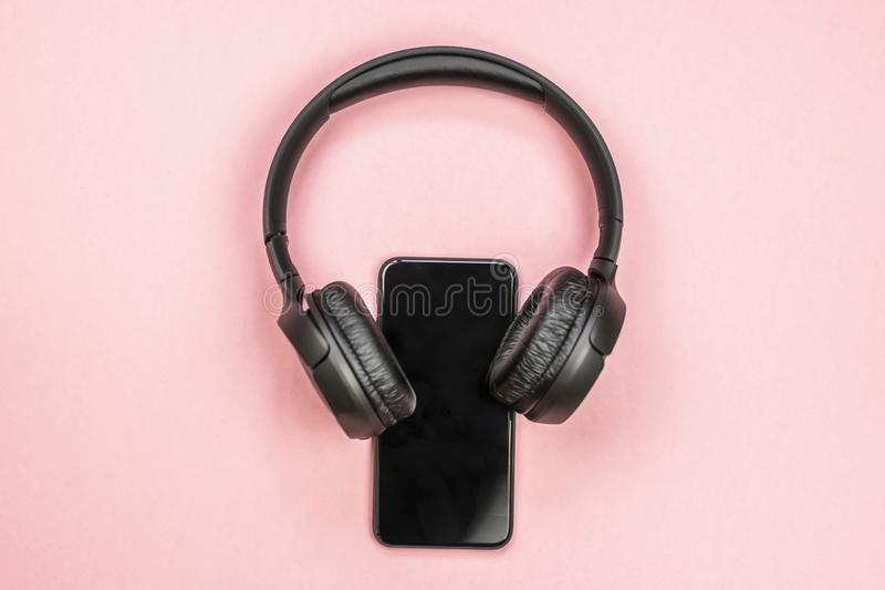 Close-up of smart phone with headphones on a pink background. stock image
