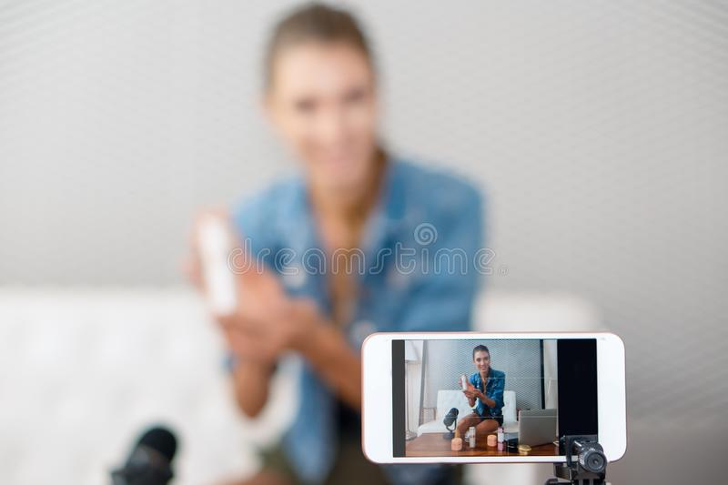 Close up of smart phone screen with video broardcasting of makeup artist youtuber demonstrating cosmetic products live online. Close up of smart phone screen royalty free stock photos