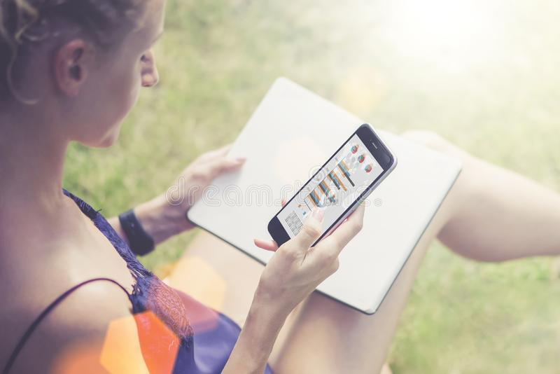 Close-up of smartphone with graphs, data, charts, diagrams on screen in hand of young woman sitting in park on lawn royalty free stock image
