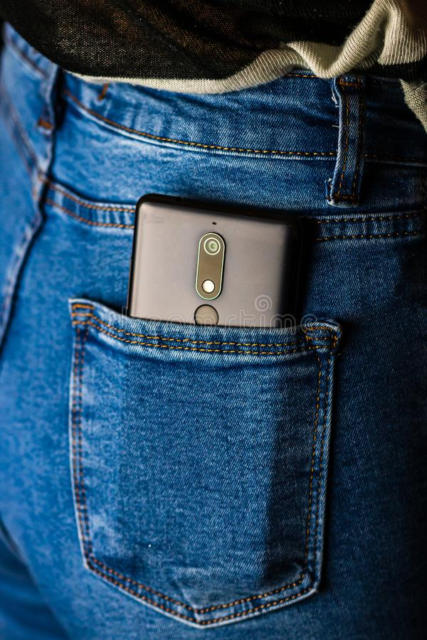 Close up smartphone in jeans back pocket. Business and fashion concept. Copy space. Denim hipster jeans stock image