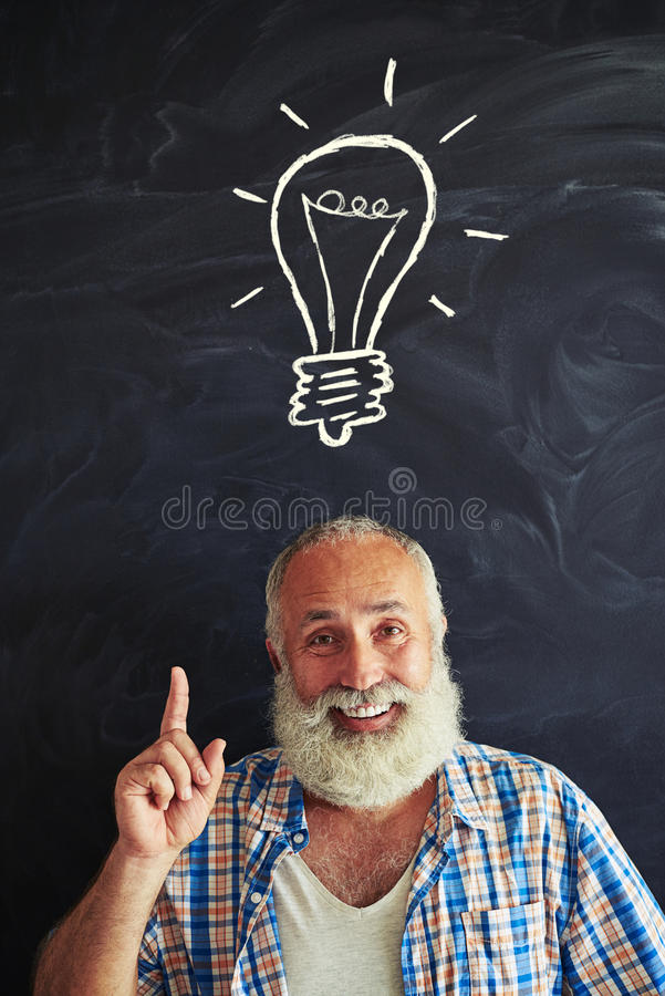 Close-up of smiling aged man pointing at chalk light bulb drawn royalty free stock images