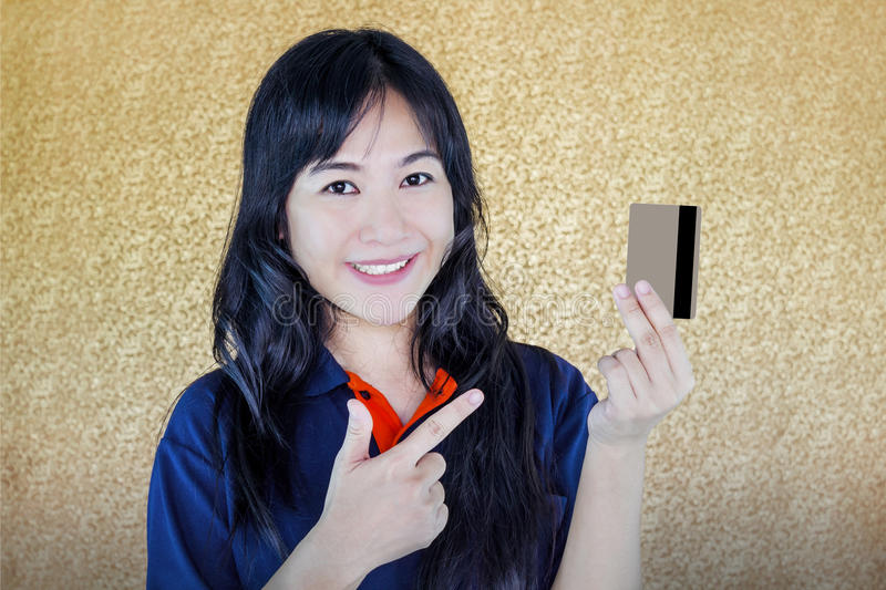 Close up smiling Asian women presenting back of debit or credit royalty free stock images