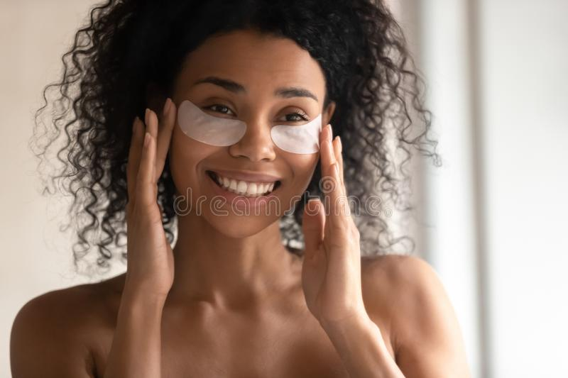 Close up of smiling biracial woman apply under-eye patches stock photos