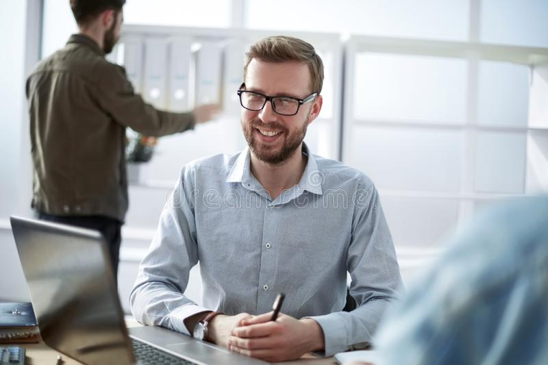 Close up. smiling businessman sitting at his Desk stock image