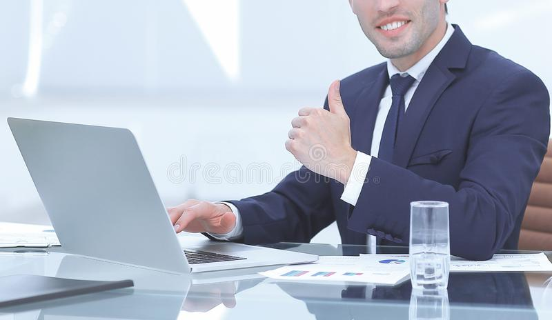 Close up.smiling businessman working on laptop and showing thumb up stock image