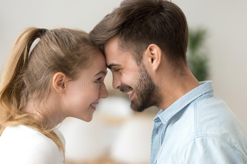 Close up smiling couple in love touching forehead, enjoying tender moment royalty free stock photo