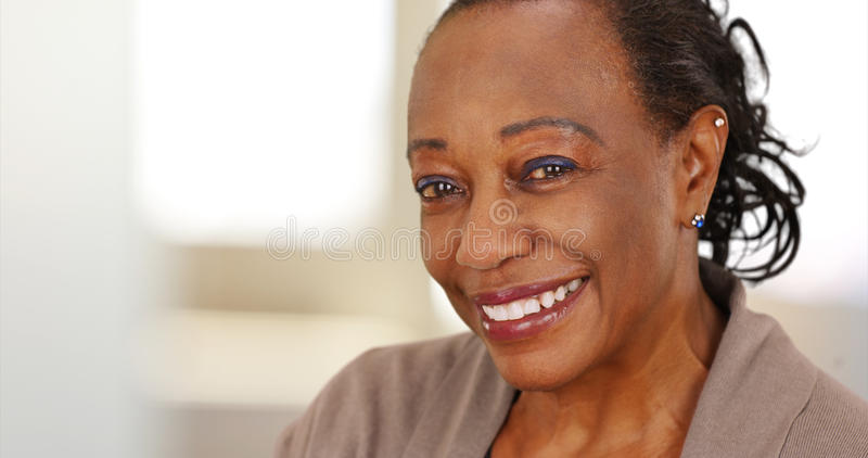 Close-up of a smiling elderly African American woman at work.  royalty free stock photography