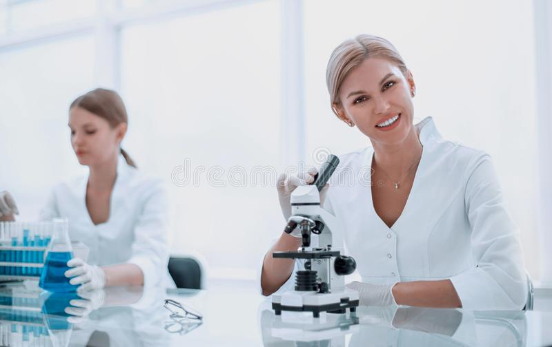 Close up. smiling female scientist sitting at her Desk stock image