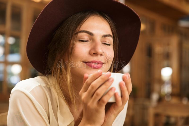 Close up of a smiling girl in hat sitting at the cafe table indoors, holding cup of te stock photography