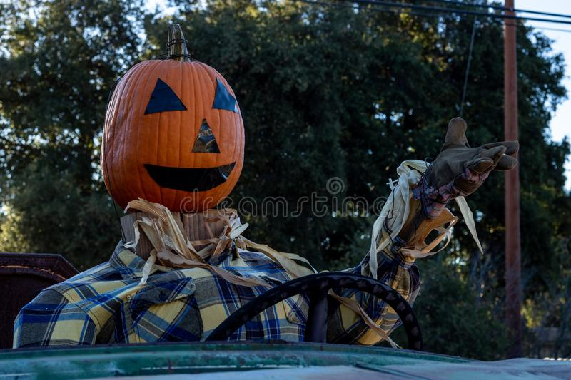 Smiling, happy, welcoming, fun friendly pumpkin head scarecrow driving an old truck to a halloween harvest party. Close-up of smiling, happy, welcoming, fun stock images