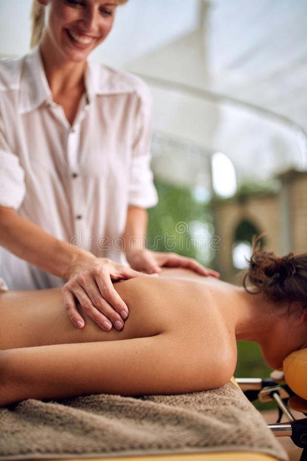 Close up of massage therapist doing a back massage on outdoor royalty free stock photo