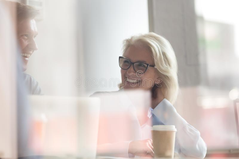 Close up of smiling diverse employees negotiate at meeting stock image