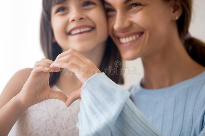 Loving mom and daughter show heart sign by hands. Close up of smiling mom and preschooler daughter hug showing heart sign with hands, happy young mother and stock photo