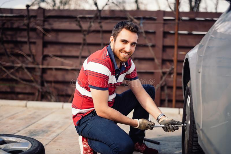 Close up smiling portrait of working man and changing tires using wrench, jack and hydraulic tools royalty free stock photography