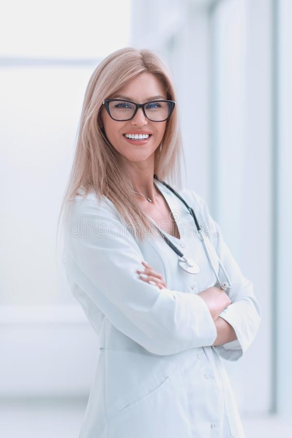 Smiling woman doctor standing near the hospital window royalty free stock photography