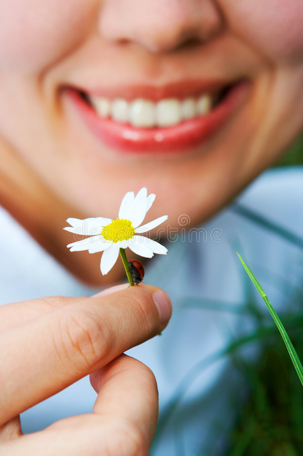 Close-up smiling woman holding flower camomile royalty free stock photography