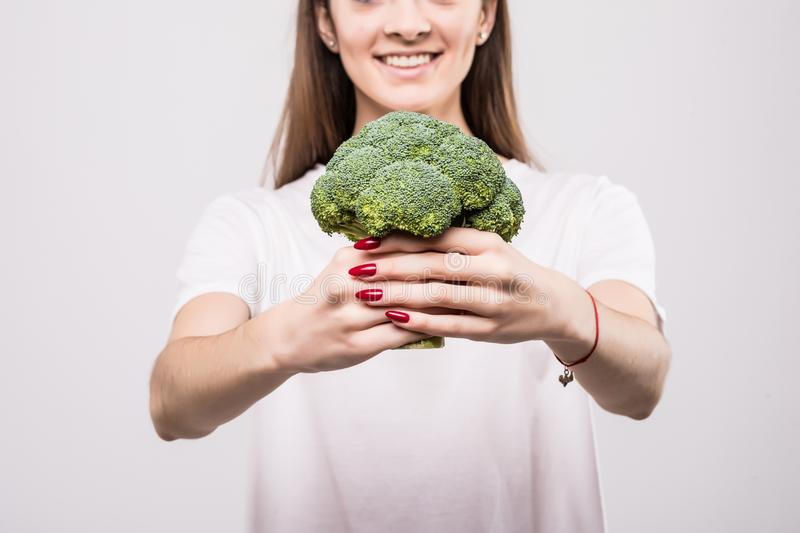 Close up of a smiling woman showing broccoli isolated over white background. Health concept. stock image