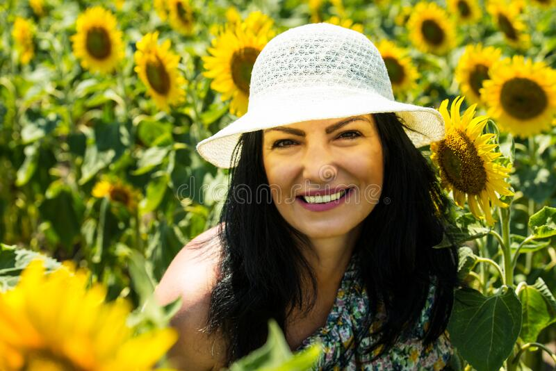 Close up of smiling woman in sunflowers field royalty free stock photo