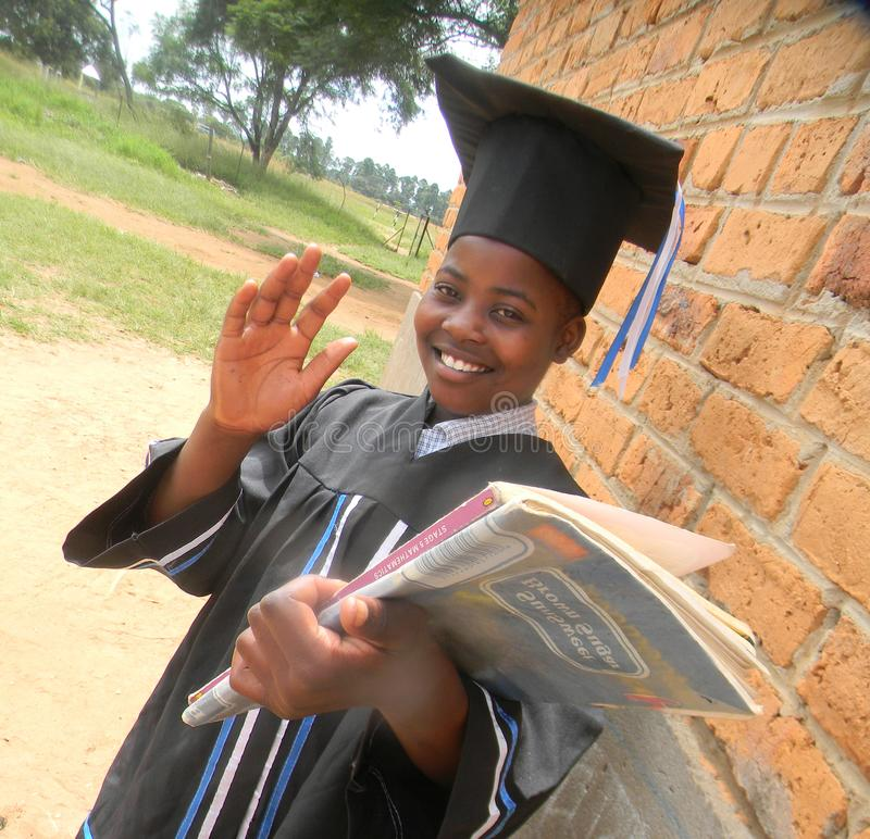 Smiling young girl in graduation attire waving hand. Close up of a smiling young black schoolgirl waring graduation robe and cap waving hand and holding books stock image
