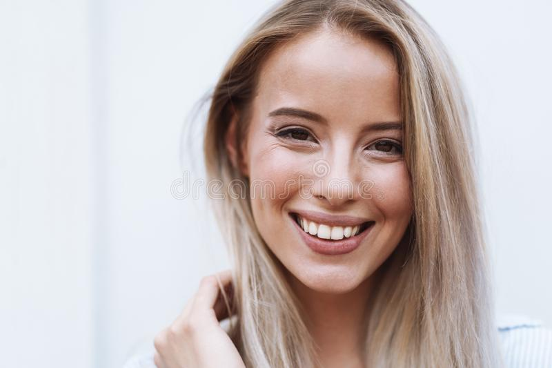 Close up of a smiling young blonde woman standing stock images