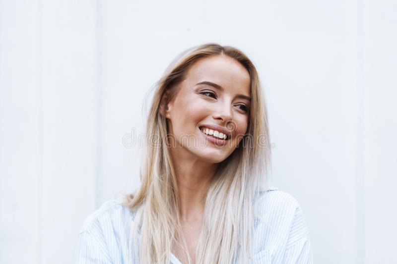 Close up of a smiling young blonde woman standing stock image