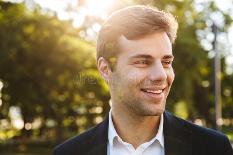 Close up of a smiling young business man walking stock image