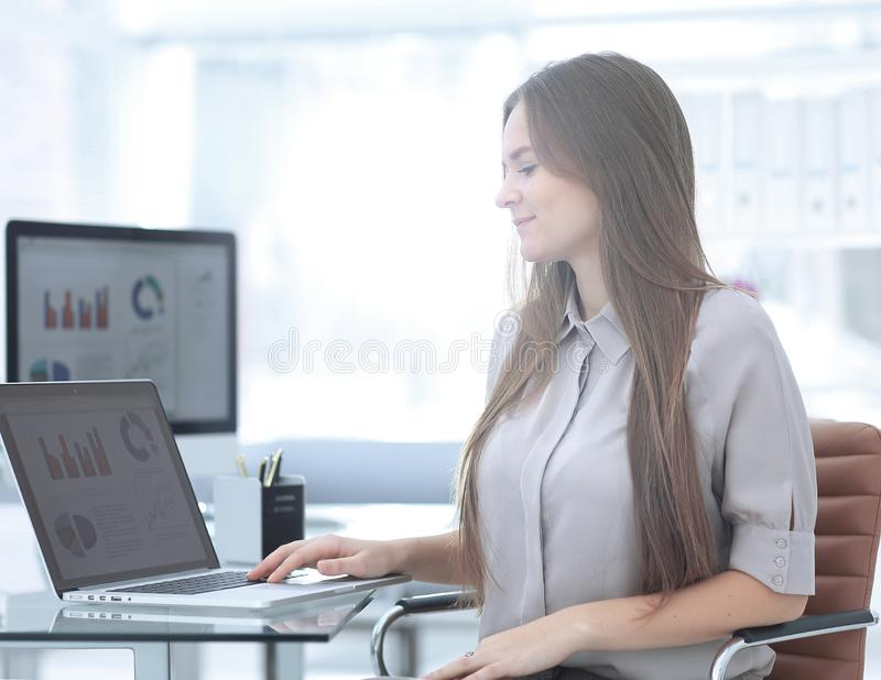 Close up.smiling young employee of the company. Sitting near the desk royalty free stock image