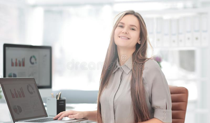 Close up.smiling young employee of the company. Sitting near the desk royalty free stock photo