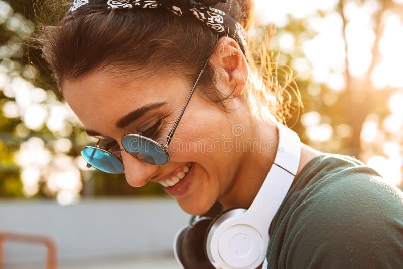 Close up of a smiling young girl. Wearing sunglasses and headphones outdoors royalty free stock photo