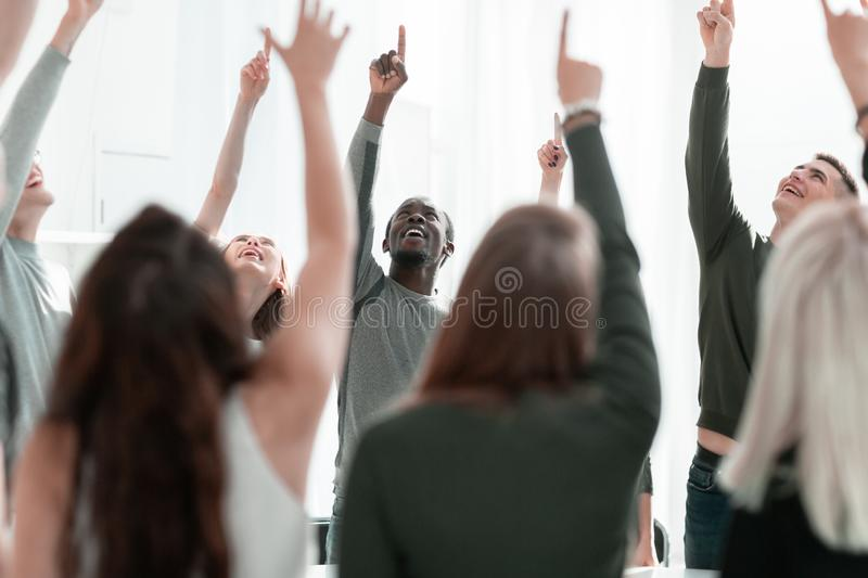Close up. smiling young people pointing up stock image
