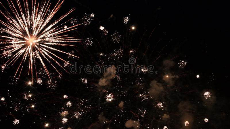 Smoke and fiery flashes of a festive firework on a black background. Abstract background of the dark sky with a salute of the new royalty free stock photos
