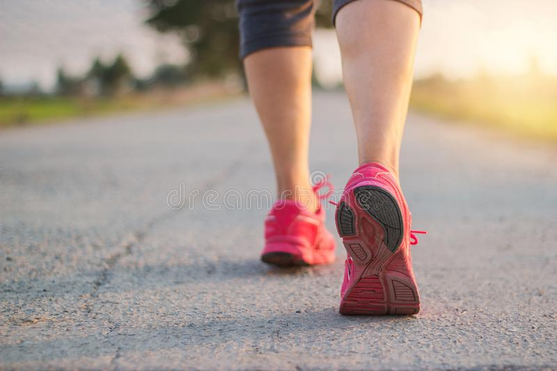 Close up sneaker of athlete woman runner feet on rural road while running exercise on sunset background royalty free stock photography