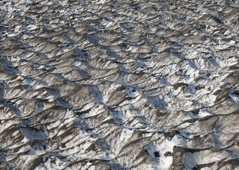 Close up snow dunes with black volcanic lava sand with reflection of blue sky. Iceland natural abstract background stock photo