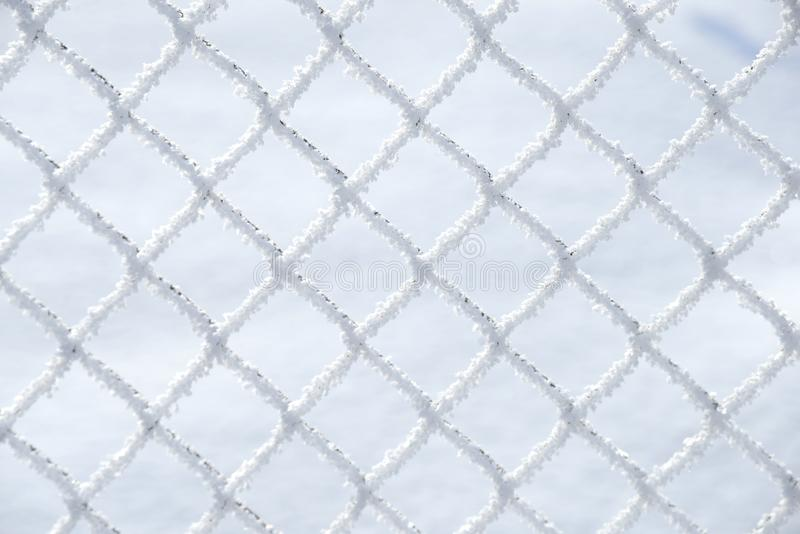 Close up of snow laying on the squares of a wire farm fence with snow in background - Image stock image