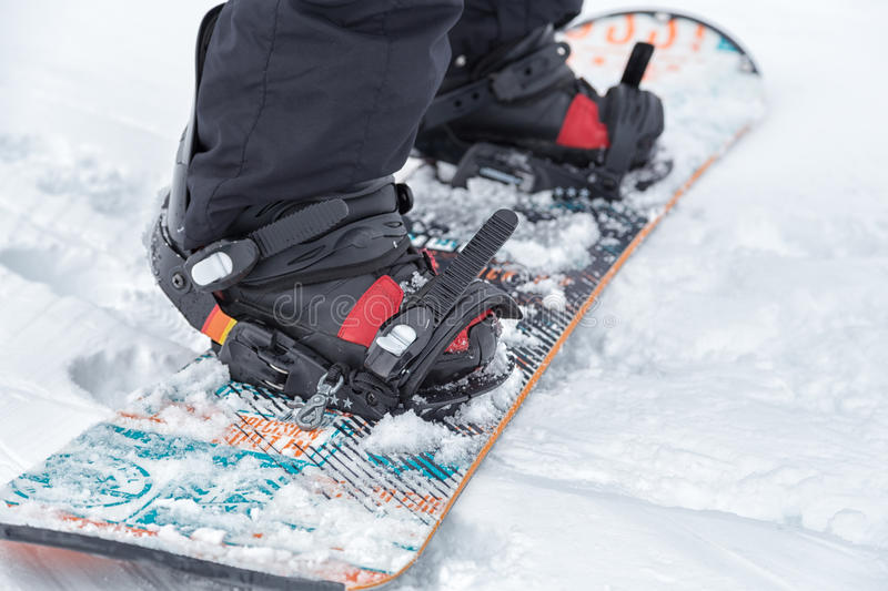 Close up of a snowboard. With bindings and the snowboard boots hooked in. The snowboard is on the snowy ground, completely white and clean stock images