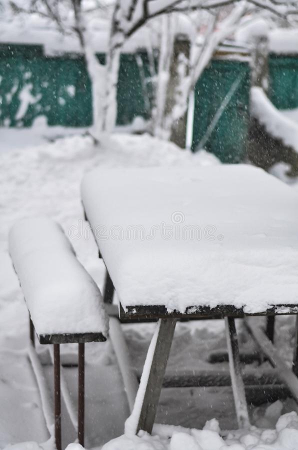 Close-up of a snowy yard with a table and benches during a snowstorm and blizzard. royalty free stock photos