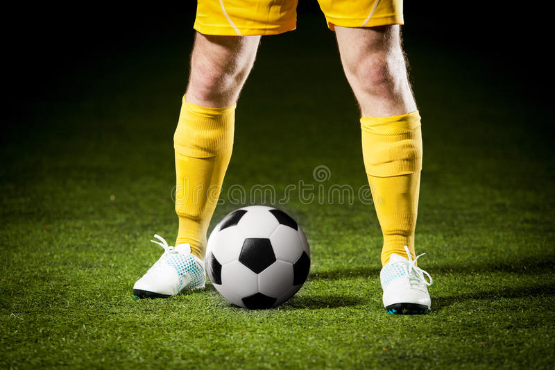 Soccer ball and a feet of a soccer player. Close up of a soccer ball and a feet of a soccer player stock images