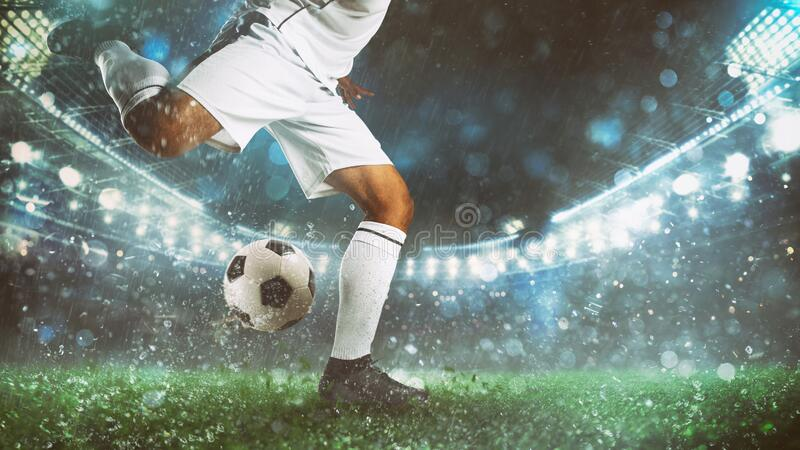 Close up of a soccer scene at night match with player in a white uniform kicking the ball with power stock photo