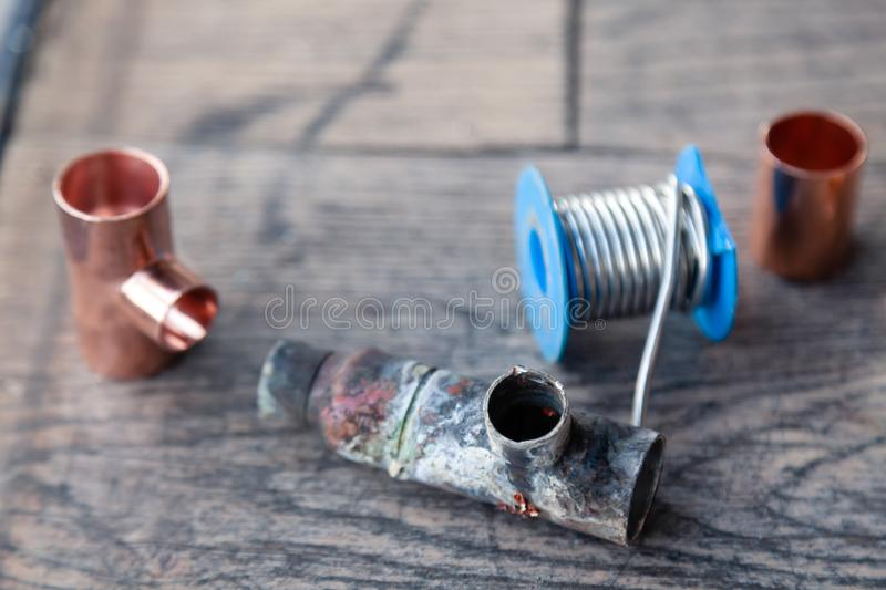 Close-up soldering, plumbing, construction professional tools, parts of copper pipes on a wooden background. Concept of royalty free stock photo
