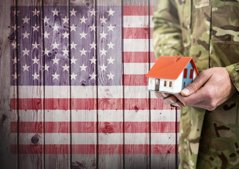 Close up of soldier holding a little house in front of american flag. Digital composite of Close up of soldier holding a little house in front of american flag stock image