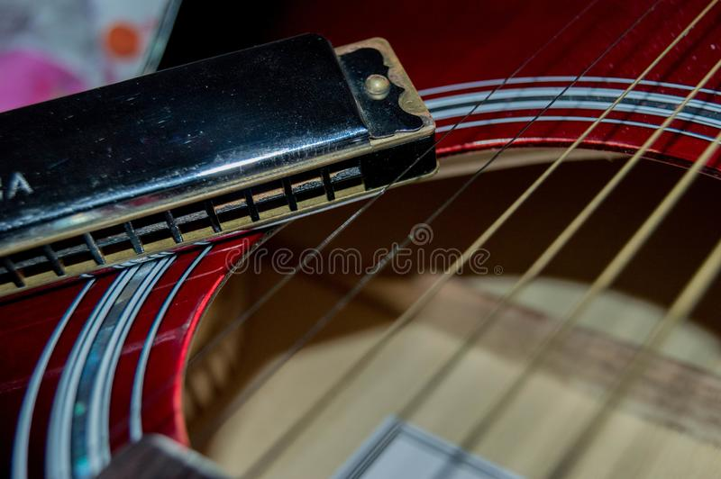 Some guitar strings next to a harmonica. royalty free stock photos