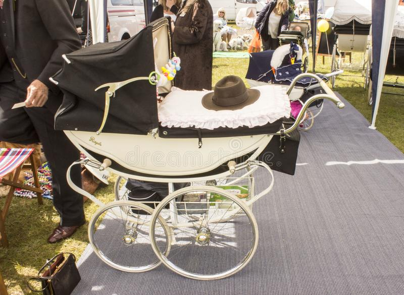 People gathered around the old fashioned prams on show stock photo